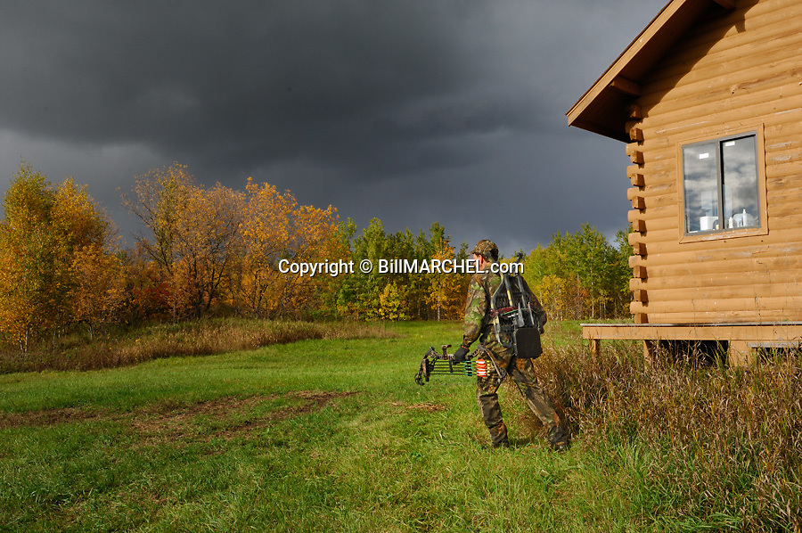 00105-044.15 Bowhunting (DIGITAL) Archer is leaving hunting shack walking to stand following storm, a great time to hunt deer.   H2L1