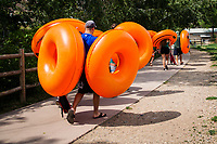 A group carrying birght orange tubes, also known as donuts or bisuits, walk the path leading upstream along Clear Creek Canyon, Golden, Colorado.