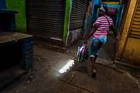 An Afro-Colombian woman, carrying purchased vegetables in the plastic bag, walks inside the market of Bazurto in Cartagena, Colombia, 14 December 2017. Far from the touristy places in the walled city, a colorful, vibrant labyrinth of Cartagena's biggest open-air market sprawls to the Caribbean seashore. Here, in the dark and narrow alleys, full of scrappy stalls selling fruit, vegetables and herbs, meat and raw fish, with smelly garbage on the floor and loud reggaeton music in the air, the African roots of Colombia are manifested.
