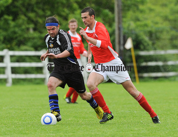 Brian Harte of West Clare FC in action against Kevin Feeley of Newmarket Celtic A during their Cup semi final game at Doora. Photograph by John Kelly.