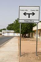 Senegal, Touba.  Street Sign Pointing Opposite Ways to the City Center.