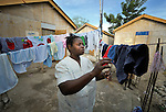 A survivor of Haiti's devastating earthquake, Beatrice Jean Louis hangs laundry in front of her new house in Leogane, south of the Haitian capital of Port-au-Prince. The houses here were built with assistance from the Christian Reformed World Relief Committee, a member of the ACT Alliance. CRWRC is planning more than 1700 houses in the community, and had about half that number completed by the first anniversary of the January 21, 2010 quake. The houses are built on the foundations of the residents' former homes, and are transitional--designed to be improved by residents as they are able. The houses have yet to receive their first coat of paint. CRWRC has also worked with community members on water and sanitation issues in response to the cholera outbreak, and is providing psycho-social support for residents as they rebuild their lives.
