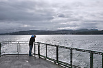 Commuters pass the time on a rainy April day enroute to San Juan Island from Anacortes aboard a Washington State Ferry.