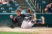 Rochester Red Wings catcher John Ryan Murphy (12) holds the ball after tagging Dariel Alvarez (12) out at home during a game against the Norfolk Tides on July 17, 2016 at Frontier Field in Rochester, New York.  Rochester defeated Norfolk 3-2.  (Mike Janes/Four Seam Images)