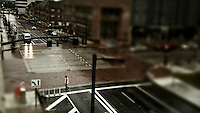 Pedestrians on sidewalks and crossing streets in the rain. Photos tiltshift from overhead parking garage.