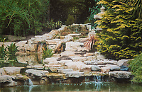 BNPS.co.uk (01202) 558833. <br /> Pic: DawnHeaver/BNPS<br /> <br /> With video - download: https://we.tl/t-5zrzRIzI4L<br /> <br /> Pictured: Waterfall rockery beside the new lake. <br /> <br /> A green-fingered couple who have spent 20 years building an incredible Japanese-themed garden behind their bungalow home are now preparing to show it off to the public. <br /> <br /> Dawn and Terry Heaver, who say they have never even visited Japan, began cultivating the three-quarter-acre plot after being inspired by a visit to a nearby botanical gardens.<br /> <br /> Their secluded garden in the village of St Ives, Dorset, is now enclosed by evergreen trees and features a waterfall, an ornamental 5,000sq ft lake, two shinto torii gates, an Oriental pergoda and Japanese stone ornaments including a tiered tower and foo dogs.