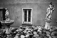 Switzerland. Canton Ticino. Tesserete. Private house. Window with wrought iron. Garden decoration. Two sculptures of young beautiful half naked women. Rocks on the ground. 15.01.2020 © 2020 Didier Ruef