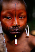 A - ukre village, Xingu Indigenous Area, Para State, Brazil. Kayapo boy with red urucum and black genipapo face paint and bead lip.