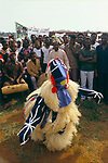 """Redemption Day celebration Monrovia Liberia, West Africa. 1983. A masked Poro dancer performs a traditional dance during the  Redemption Day celebration.  The banner reads """"The Belle Citizens of Lofa County..."""""""