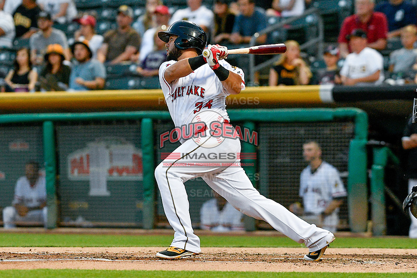 Juan Graterol (34) of the Salt Lake Bees follows through on his swing against the Albuquerque Isotopes during the Pacific Coast League game at Smith's Ballpark on August 29, 2016 in Salt Lake City, Utah. The Isotopes defeated the Bees 9-4. (Stephen Smith/Four Seam Images)