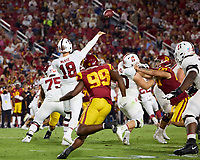 LOS ANGELES, CA - SEPTEMBER 11: Tanner McKee #18 of the Stanford Cardinal passes the ball under pressure from Drake Jackson #99 of the USC Trojans during a game between University of Southern California and Stanford Football at Los Angeles Memorial Coliseum on September 11, 2021 in Los Angeles, California.