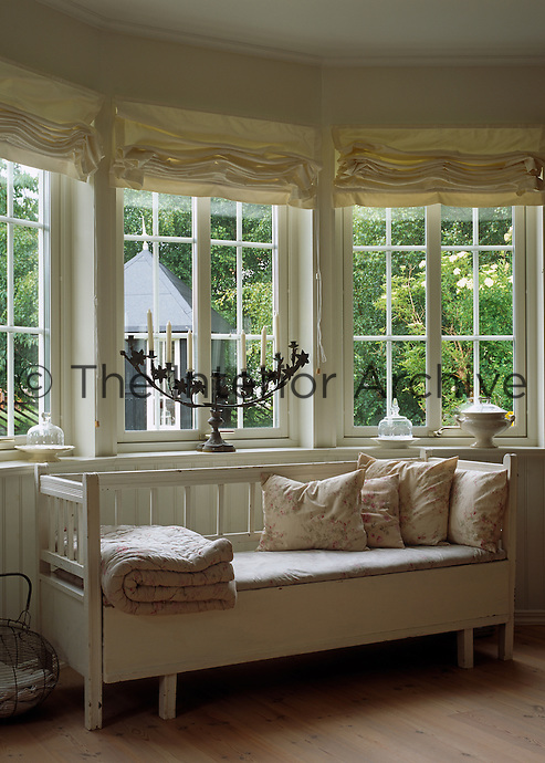 Floral print cushions and a folded quilt on a white painted daybed beside the bay window in this living room