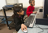 MR / Schenectady, NY. Zoller Elementary School (urban public school). Kindergarten inclusion classroom. Students (girl left, 5; boy right, 6, African American & Puerto Rican American) using computers at learning center time. MR: Ram13, Car38. ID: AM-gKw. © Ellen B. Senisi.