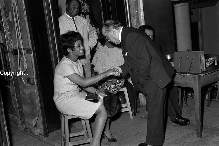 """23 février 1967. Plan rapproché sur scène, vue des coulisses, de Monsieur Louis Izar (directeur général du Théâtre du Capitole) serrant la main de la chanteuse Olive Moorefield. En arrière plan, debout, le chanteur William Rey. Observation: Répétion, au Théâtre du Capitole de l'opéra américain """"Porgy and Bess"""", Musique de geoge Gershwin, à l'occasion du 30ème anniversaire de sa mort."""