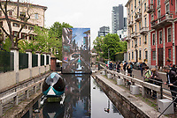 "Milano, Salone del Mobile. ""Aqua"", Installazione alla conca dell'Incoronata del Naviglio Martesana, raffigurante una Milano futuristica con un mezzo di ""boat sharing"" sul naviglio reso navigabile --- Milan, Salone del Mobile. ""Aqua"", installation on the Naviglio Martesana. A futuristic Milan is shown on a led panel and a ""boat sharing"" capsule lies on the canal turned navigable"