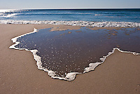 Run-off from ocean wave creates unusual Texas-style shape on sand