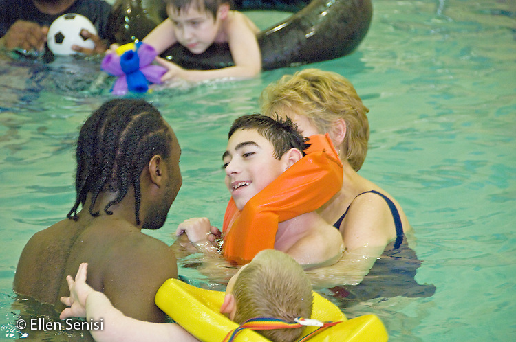MR / Albany, NY.Langan School at Center for Disability Services .Ungraded private school which serves individuals with multiple disabilities.Teaching assistants, occupational therapists, and students interact in the pool during gym class. Students in this class swim once a week as part of their physical education program..MR: AH-cfds.© Ellen B. Senisi
