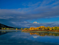 749450326 clouds from a clearnig storm hide all but the peak of mount moran along the oxbow bend with aspens in brillilant yellow fall color on the snake river in grand tetons national park wyoming