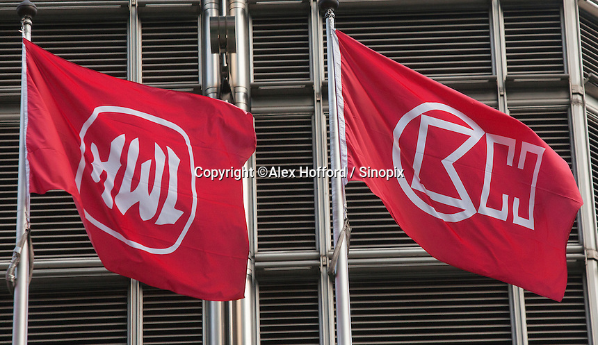 The flags of Hutchison Whampoa Limited and Cheung Kong Holdings fly outside the Cheung Kong Center, Central district, Hong Kong, China, 28 April 2014.