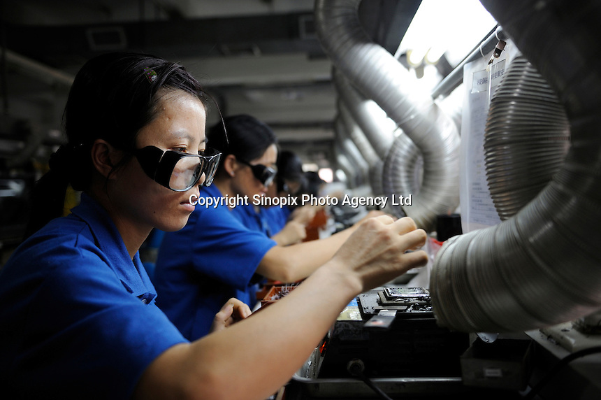 Chinese workers work at an electronic plant processing for a US modular jacks and plugs manufacturer in Dongguan, Guangdong, China..