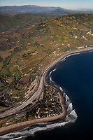 aerial photograph of Rincon Point and Rincon Beach Park, Santa Barbara County, California in spring, State Highway 1 and mountainside farming in the background