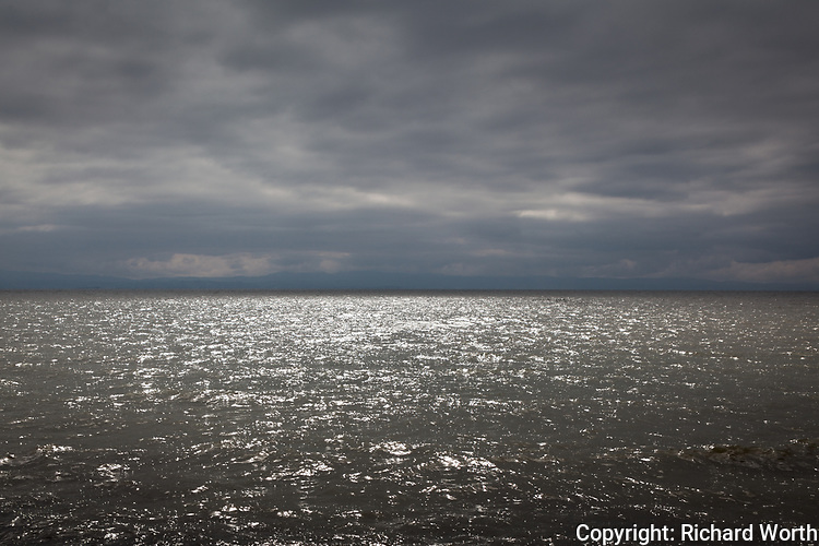 Dark clouds fill the sky over San Francisco Bay while a break in the clouds outside of the camera's view allows sunlight to set a portion of the bay alight with glistening, bright and shining ripples.