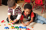 Education preschool first days of school 2-3 year olds two boys playing side by side with toy vehicles cars