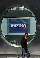 Locals pass Mizuho Bank in Tokyo, Japan. Mizuho Financial Group Inc., the Japanese bank with the biggest subprime writedowns in Asia, posted its second straight quarterly loss as the value of its stock slumped and bad loans rose. The company turned to a 145.1 billion yen ($1.6 billion) deficit in the three months ended Dec. 31 from a 66 billion yen profit a year earlier...