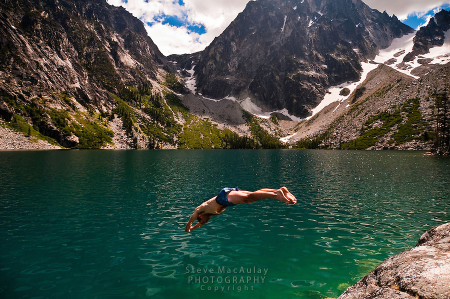 Man diving into the emerald green water of Colchuck Lake, Alpine Lakes Wilderness, WA.