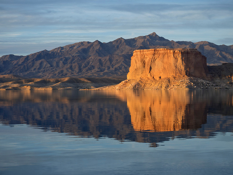 The Temple glows at sunset and reflects into the glass-like waters of the Colorado River in Lake Mead in the Lake Mead National Recreation Area on the Arizona-Nevada border (Photo from Arizona looking across to Nevada)