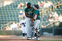 Greensboro Grasshoppers catcher Dylan Shockley (29) meets with starting pitcher Tahnaj Thomas (17) during the game against the Winston-Salem Dash at Truist Stadium on June 17, 2021 in Winston-Salem, North Carolina. (Brian Westerholt/Four Seam Images)