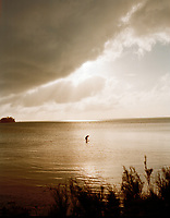 The sun breaks through a storm cloud above a lone Bermudan fisherman.