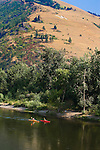 Two kayakers paddle at the base of Mount Sentinel on the Clark Fork River in Missoula, Montana