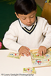 Education Preschool 3-5 year olds boy sitting at table playing with wood peg puzzle vertical
