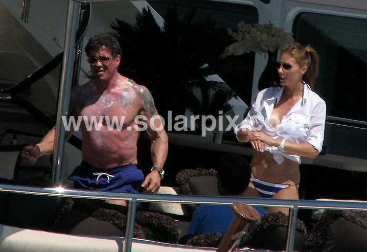 **ALL ROUND PICTURES FROM SOLARPIX.COM**.**WORLDWIDE SYNDICATION RIGHTS EXCLUDING SPAIN - NO PUBLICATION IN SPAIN**.Rocky star Sylvester Stallone looked relaxed as he sucked on a large Cuban cigar on board his luxury holiday yacht on the coast of Ibiza..The Hollywood hardman sported tattoos on both arms as he strutted around the deck with wife Jennifer Flavin..JOB REF: 6952    IBZ      DATE:  03.08.08.**MUST CREDIT SOLARPIX.COM OR DOUBLE FEE WILL BE CHARGED* *UNDER NO CIRCUMSTANCES IS THIS IMAGE TO BE REPRODUCED FOR ANY ONLINE EDITION WITHOUT PRIOR PERMISSION*
