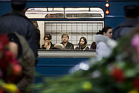 Moscow, Russia, 30/03/2010..Passengers in a Moscow Metro carriage stare at a makeshift shrine on the spot inside Park Kultury metro station where a female suicide bomber blew herself up the previous day. At least 39 people were killed and 80 injured in the double blasts at Moscow metro stations during the morning rush hour.