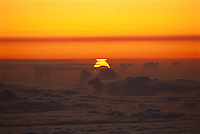 Partial eclipse of the Sun, viewed at sunrise from Mauna Kea, Hawaii.