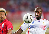 Chun Soo Lee (14) of the Korea Republic watches William Gallas (5) of France wind up a shot.The Korea Republic and France played to a 1-1 tie in their FIFA World Cup Group G match at the Zentralstadion, Leipzig, Germany, June 18, 2006.