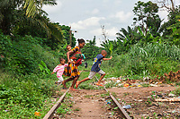 Nigeria. Enugu State. Agbani. A mother and her three children run and cross railway tracks. The train has stopped working for 25 years due to political decisions. Flip-flops are a type of sandal, typically worn as a form of casual wear. They consist of a flat sole held loosely on the foot by a Y-shaped strap known as a toe thong that passes between the first and second toes and around both sides of the foot or can be a hard base with a strap across all the toes (these can also be called sliders). 4.07.19 © 2019 Didier Ruef