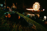 With the Ferris sheel twirling behind her, Susan Stober stretches out and enjoys a clear view of the nighttime audience packing the grandstand at the Tunbridge Fair in Vermont.