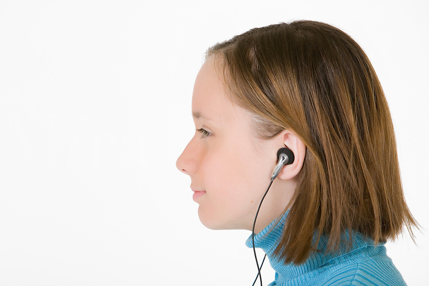 A young female teenager listens to music on her MP3 player using headphones.