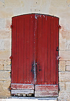 An old red wooden door on one of the winery buildings Chateau Kirwan, Cantenac Margaux Medoc Bordeaux Gironde Aquitaine France