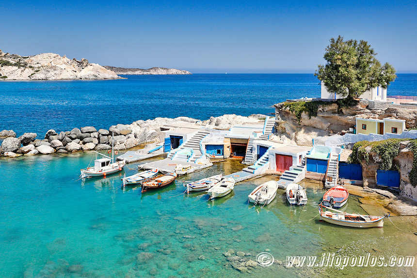"""Traditional fishermen houses with the impressive boat shelters, also known as """"syrmata"""" in Mandrakia of Milos, Greece"""
