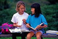 Two young girls sit on an outdoor bench sharing conversation and laughter while holding their schoolbooks. Muted green foliage in background.