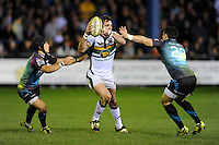 Jon Clarke of Northampton Saints (centre) offloads as he is tackled by Matthew Morgan (left) and Kristian Phillips of Ospreys during the LV= Cup second round match between Ospreys and Northampton Saints at Riverside Hardware Brewery Field, Bridgend (Photo by Rob Munro)