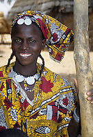 Delaquara, Niger. Young  Fulani Woman in Boubou, wearing Coins as Necklace and Jewelry.  Light Facial Scarffication, a form of tribal identification, can be seen on her forehead, her cheeks, and on either side of her mouth.