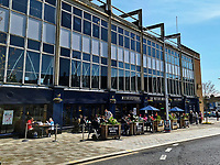 Pictured: People enjoy the sunny weather having a drink at the Potter's Wheel in Swansea, Wales, UK. Monday 26 April 2021<br /> Re: Lockdown rules caused by the Covid-19 Coronavirus pandemic have been relaxed, with outdoors pubs, restaurants and cafes now open in Wales, UK.