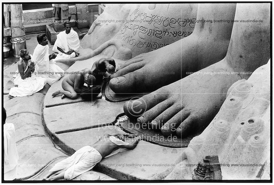 INDIA Karnataka, nude  Jain monk at feet of Jain statue of Lord Bahubali during festival Mahamastakabisheka which takes place every 12 years in Sravana Belagola / INDIEN Festival der Jainas in Shravana Belagola , nackter Jain Moench am Fuss der Statue von Lord Bahubali , das Fest findet alle 12 Jahre statt - copyright Joerg Boethling, also as signed black white Baryt fine print available!