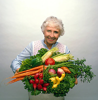 Senior woman (model) holds a large container of fresh vegetables, mostly home-grown. Little Rock, Arkansas.