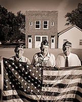 Portrait of three veterans holding an American flag and posing outside of an American Legion building.